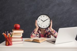 Smart girl sitting with stack of books and laptop, holding big clock, covering face